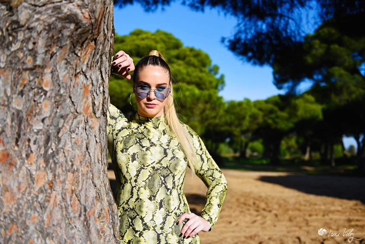 modelo mujer en una sesion fotografica en un pinar apoyada en un arbol con gafas de sol azules y traje imitando la piel de serpiente